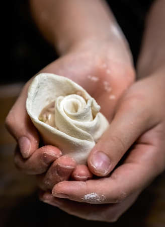 Girl holding in her hands dough shaped into rose flower petals during chinese dumpling making and cooking class in a travelers hostel, Chengdu, Sichuan Province, China