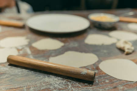 Wooden rolling pin which will be used for the making of traditional chinese dumplings during cooking class in a travellers hostel, Chengdu, Sichuan Province, China