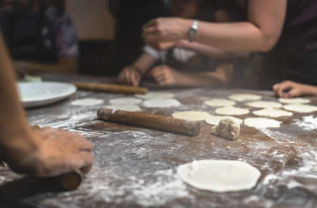 Wooden rolling pin and portioned flat dough which will be used for the making of traditional chinese dumplings during cooking class in a travellers hostel, Chengdu, Sichuan Province, China