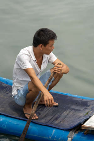 Yangshuo, China - August 2019 : Man sitting on the small bamboo boat on the shore of the Li river, the ferry crossing point Editorial