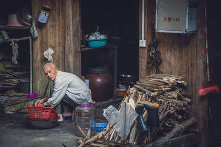 Pingan, China -  August 2019 : Poor old man doing house chores outside his wooden hut in Ping An Village, Longji Rice terraces, Guangxi Province Editorial