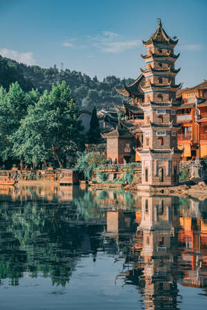 Feng Huang, China - August 2019 : Landmark Fenghuang Wanming Pagoda Tower on the riverbank of Tuo river, flowing through the centre of Feng huang Old Town