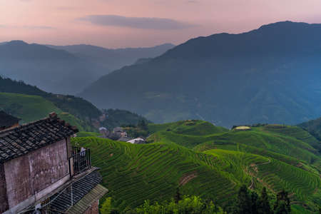 Sunset over Seven Stars Accompany the Moon cascading layered Rice Terraces forming part of Longji Rice Terraces, Pingan village, northern Guilin, Guangxi Zhuang Autonomous Region aka Guangxi Province, China