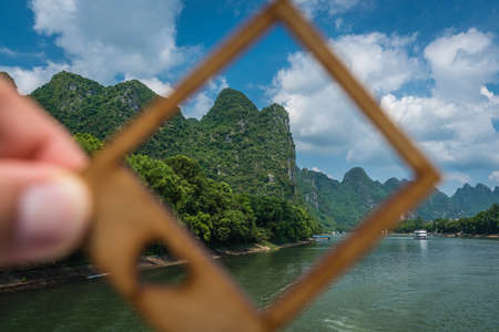 Man holding a small picture frame covering green karst peak dotting the banks of the magnificent Li river flowing from Guilin to Yangshuo, China