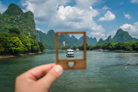 Sightseeing boat full of tourists in a frame on a trip on the magnificent Li river from Guilin to Yangshuo, China