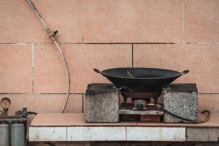 Old black metal pan wok on a gas cooker on a street food stall in China