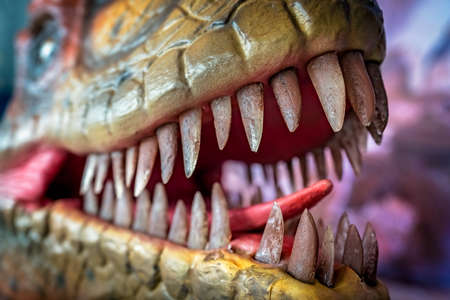 Open mouth showing sharp teeth of a Velociraptor dinosaur statue