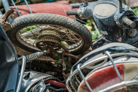 Yangshuo, China - August 2019 : Used, old, damaged and disposed of motorbikes, motorcycles and scooters piled up in the yard outside metal recycling plant in Yangshuo, Guangxi Province