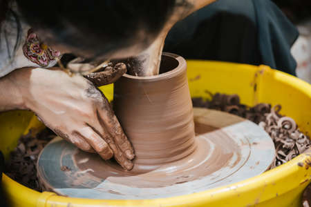 Chongqing, China - August 2019 : Female worker sitting in a workshop making ceramic pottery for sale, Ci Qi Kou Old town Editoriali