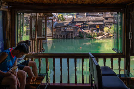 Feng Huang, China -  August 2019 : Chinese man and woman holding feet in a water tank filled with rufa garra fishes in chinese spa pedicure skin care treatment, Fenghuang Old Town, Hunan Province