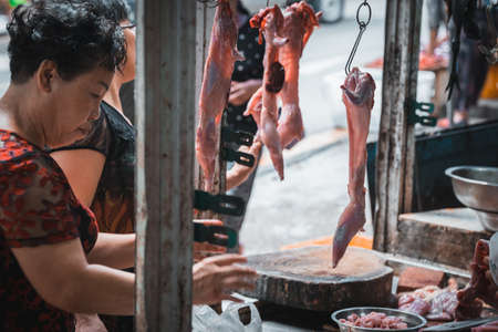 Zigong, China - July 2019 : Woman checking the freshness and quality of rabbit meat on the hooks in street butcher shop in Zigong town, Sichuan Province