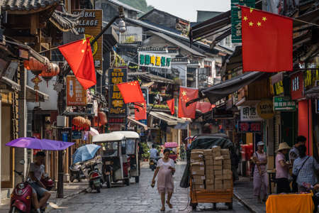 Yangshuo, China - August 2019 : Old town street lined with souvenir shops in the centre of Yangshuo town, Guangxi Province