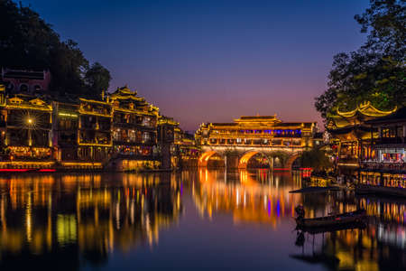 Feng Huang, China - August 2019 : Feng Huang, China - August 2019 : Illuminated at night old historic arched bridge on the riverbanks of Tuo river, flowing through the centre of Fenghuang Old Town