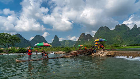 Yangshuo, China - August 2019 : Bamboo raft carrying tourists being lifted up on the conveyor belt lift on the trip on the scenic and beautiful Yulong River