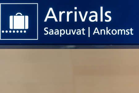 Blue airport arrivals sign board in Helsinki, Finland