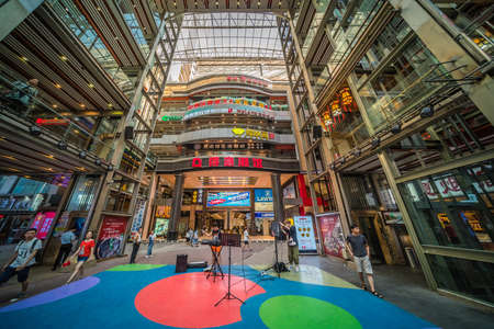 Chongqing, China - August 2019 : Music band setting up music equipment to perform inside of the modern commercial and business shopping centre building in the Jiefangbei district in the downtown of Chongqing city