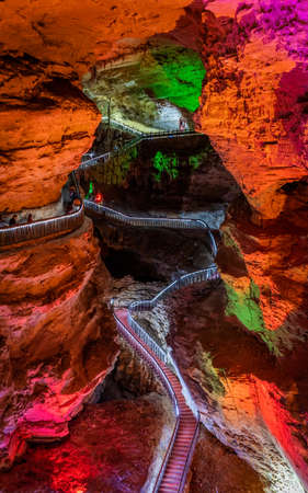 Zhangjiajie, China -  August 2019 : Tourists walking on the iluminated trail path inside the stunning and beautiful Huanglong Yellow Dragon Cave called also the Wonder of the World`s Caves