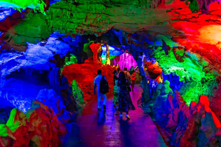 Zhangjiajie, China -  August 2019 : Group tour of people walking inside the stunning illuminated interior of the beautiful Huanglong Yellow Dragon Cave called also the Wonder of the World`s Caves, Zhangjiajie, Hunan province