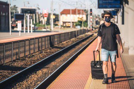 Middle aged male man wearing protective face mask, pulling a wheeled luggage trolley standing alone on an empty platform awaiting arrival of a scheduled train, traveling in the time of covid19 pandemic 免版税图像
