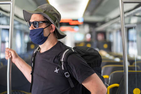 Middle aged male man with a backpack, wearing protective face mask, standing alone in almost empty train carriage, traveling in the time of covid19 pandemic 免版税图像