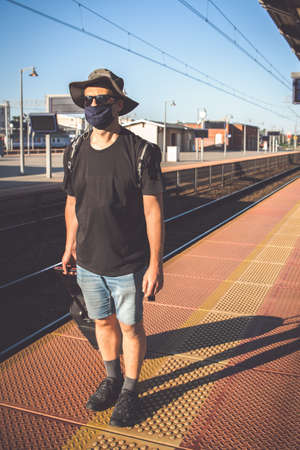 Middle aged male man wearing protective face mask, pulling a wheeled luggage trolley standing alone on an empty platform awaiting arrival of a scheduled train, traveling in the time of covid19 pandemic