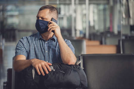 Middle aged male man with a backpack, wearing protective face mask, sitting alone in almost empty airport departure lounge and checking his mobile phone for incoming messages, traveling in the time of covid19 pandemic