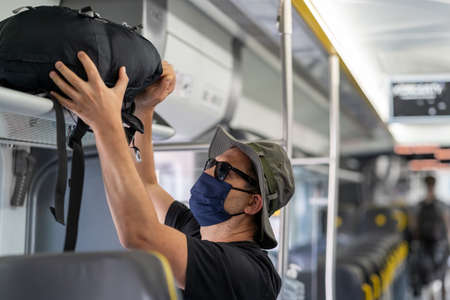 Middle aged male man wearing protective face mask, putting his backpack on above seat on a shelf in almost empty train carriage, traveling in the time of covid19 pandemic