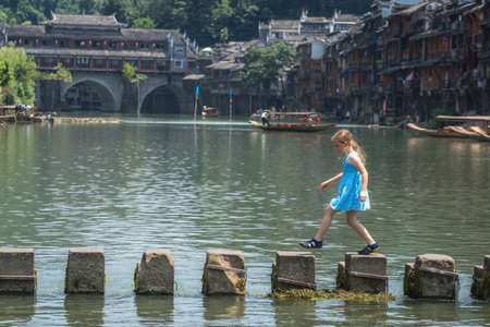 Young Caucasian girl crossing waters on stepping stones on Tuojiang river, flowing through the centre of Fenghuang Old Town, China Stock Photo