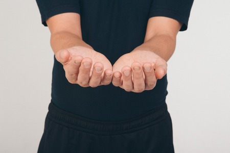 A man in a black t-shirt holds his hands in front of him palms up