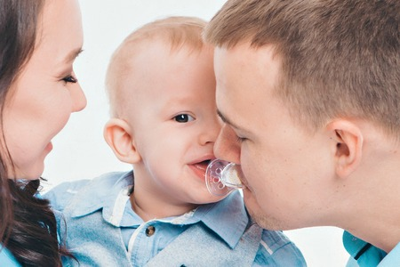 baby on the hands of parents on a white background. dad takes a mouth a pacifier from a baby