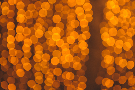 many blurred small electric bulbs on a wall. Yellow blurred lights. Wall of Christmas lights 免版税图像