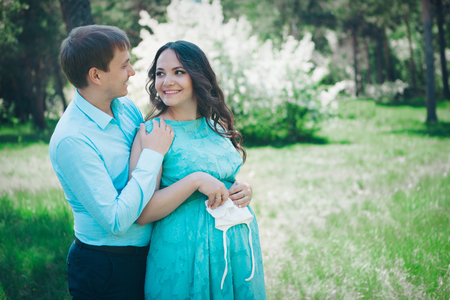 Man hugs his pregnant woman from behind standing in the forest. fashion for pregnant woman