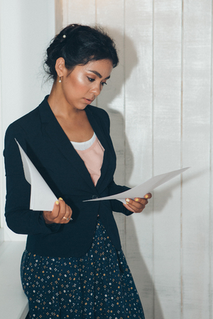girl in a business suit Asian appearance on a white background in the office working with documents