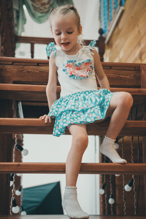 a little blond girl in a white and blue dress in polka dots and light socks descends a wooden ladder crawling 免版税图像