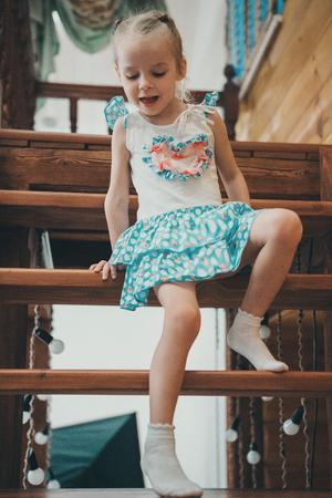 una niña rubia con un vestido blanco y azul con lunares y calcetines ligeros desciende una escalera de madera arrastrándose