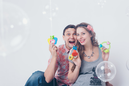 pregnant woman and ,man playing with rattle on floor on white background