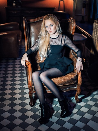 Portrait of a blue-eyed blonde in black clothes. Beautiful girl looking at the camera. Woman with loose hair