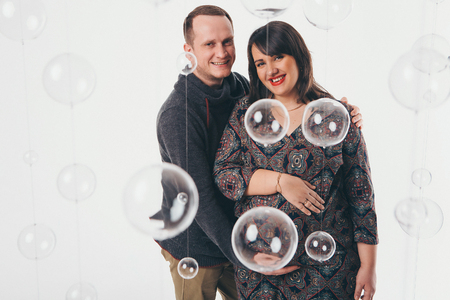 Family portrait: the husband embraces the pregnant wife on a white background. pregnant couple in love