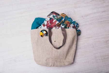 fabric bag filled with clothes and fabrics with bird icon on white background