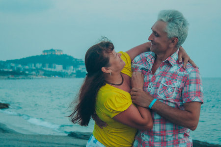 an elderly couple holding hands against the sea. Gray-haired man hugs a woman