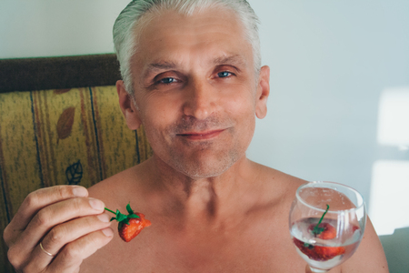 Portrait of a man with a glass and strawberries. pensioner drinks water with fruit Foto de archivo