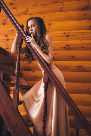 beautiful girl posing on the stairs in a pink long dress. Model in evening dress for prom