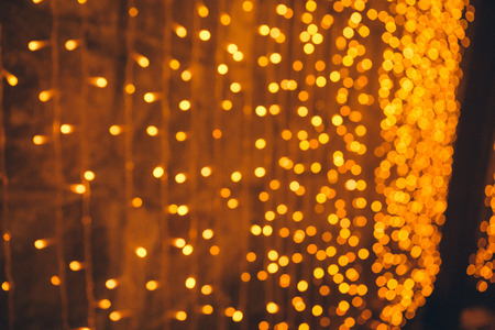 many blurred small electric bulbs on a wall yellow blurred lights wall of christmas
