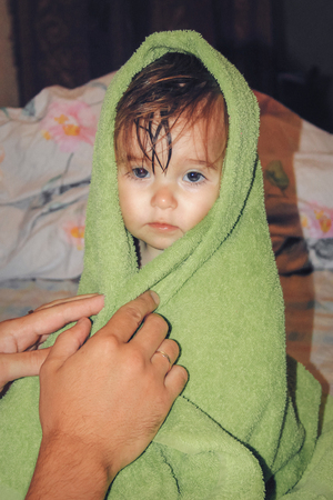 a child with wet hair wrapped in a green towel. Healthy lifestyle Stock Photo