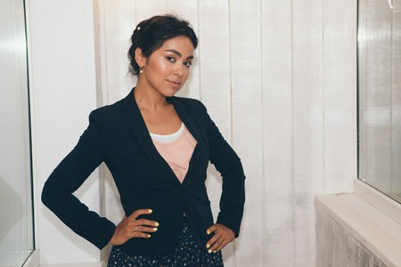 Asian woman in a black suit posing in front of the camera on a white background