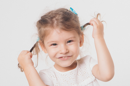 portrait of little beautiful girl with pigtails who laughs on white background