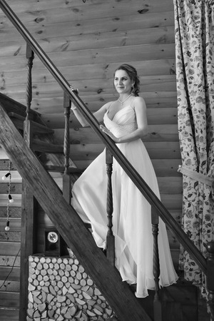 a woman in a white dress leaned against the railing of the stairs