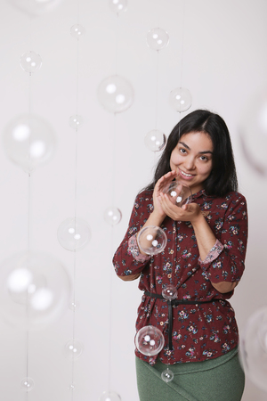 beautiful girl among the glass balls one of which she holds in her hands Stock Photo