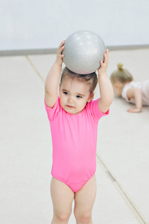 a little girl in a pink swimsuit doing gymnastics with a small ball Stock fotó