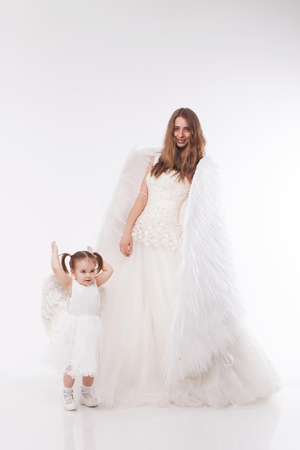 a woman and a girl in white dresses with angel wings on his back. Big and small angel on white background